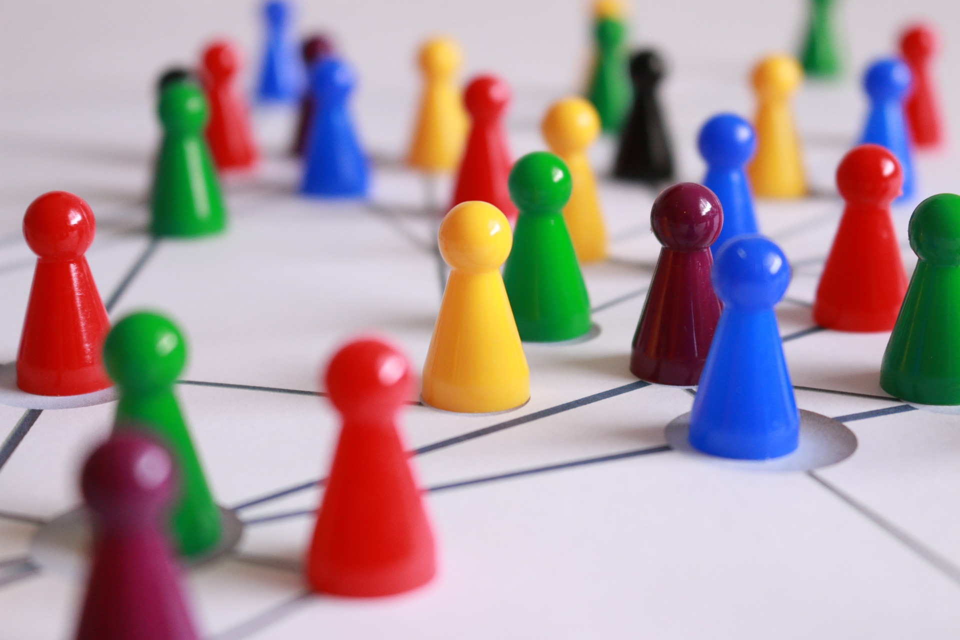 Spielfiguren auf einem gezeichneten Netzwerk symbolisieren Gruppenbeziehungen